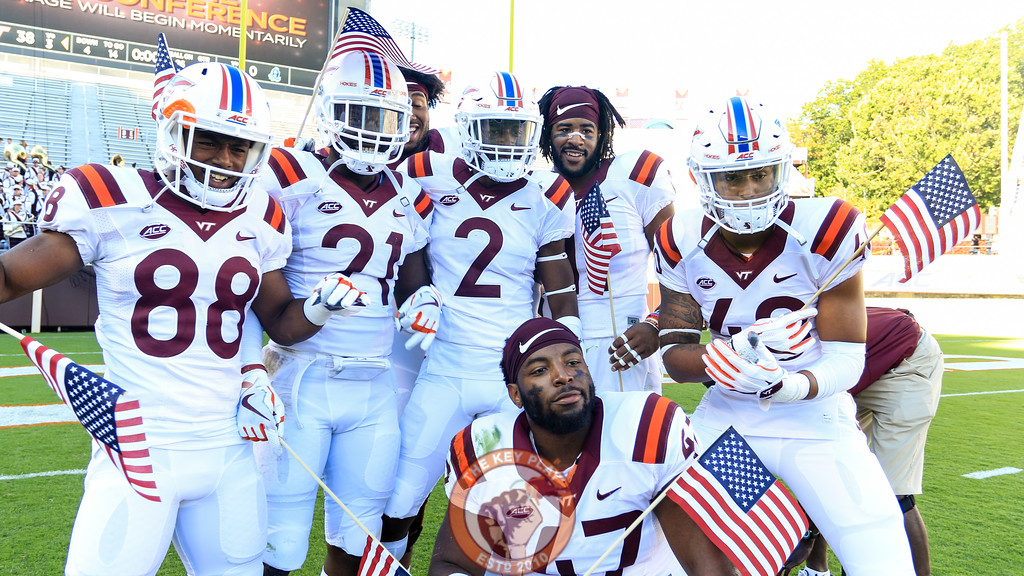 A group of Hokies pose with American flags after the end of the game. The game was a part of Military Appreciation Day at Lane Stadium. (Mark Umansky/TheKeyPlay.com)