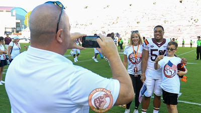 LB Andrew Motuapuaka poses with a young fan and his family for a photo as the Hokies walk off the field. Virginia Tech defeated ODU 38-0 to start the season 4-0. (Mark Umansky/TheKeyPlay.com)