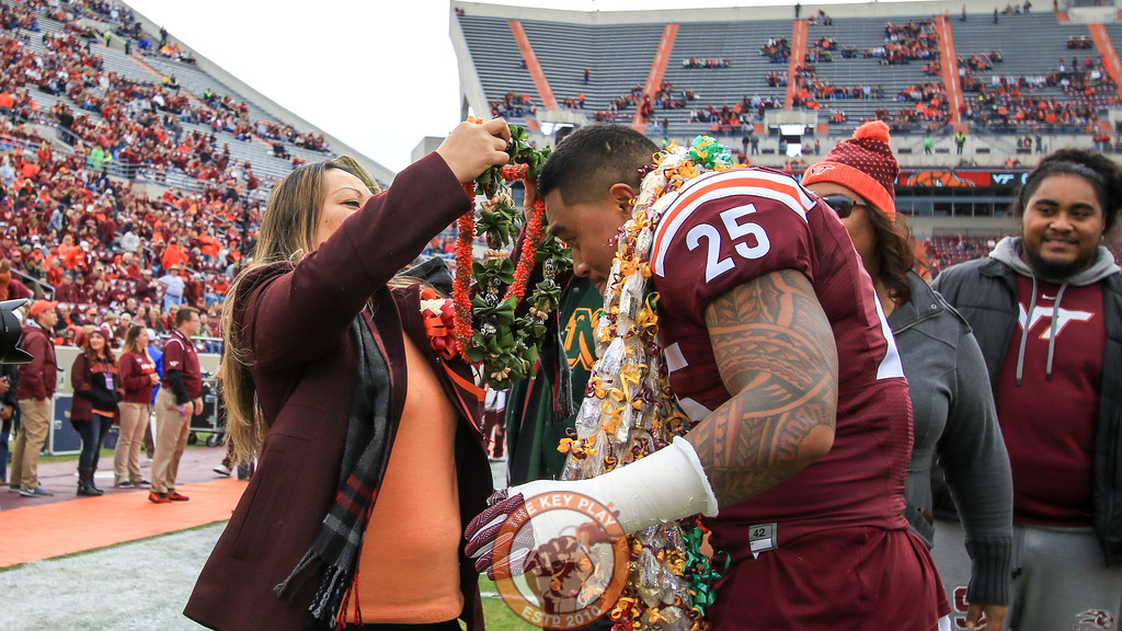 Andrew Motuapuaka greets his family on the field during senior day festivities before the game. (Mark Umansky/TheKeyPlay.com)
