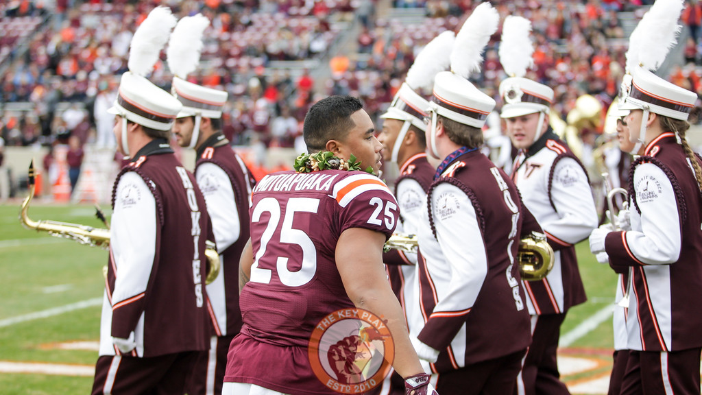 Andrew Motuapuaka looks for an opening through the band as he attempts to rejoin his team before heading back to the locker room. (Mark Umansky/TheKeyPlay.com)