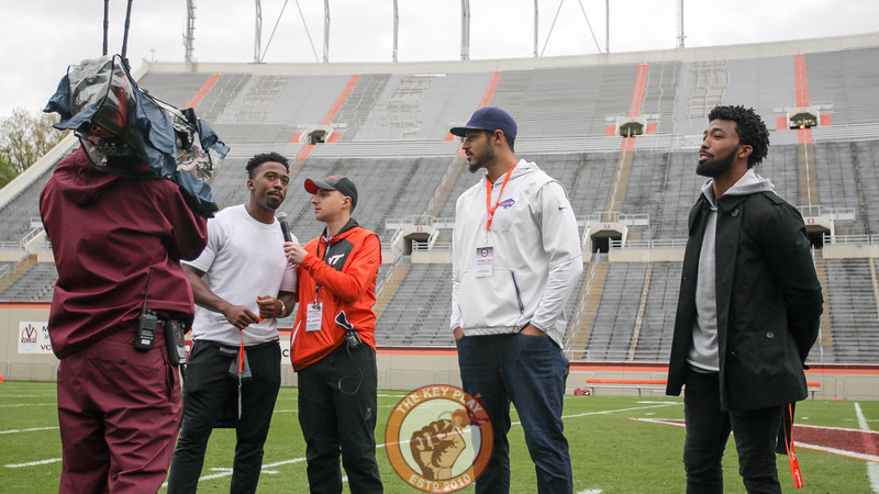 Former Virginia Tech players Tyrod Taylor (left), Logan Thomas (center), and Kendall Fuller (right) get interviewed on the field during a break between quarters. (Mark Umansky/TheKeyPlay.com)