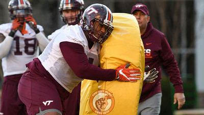 Virginia Tech Hokies defensive tackle Tim Settle (4) unloads a big hit on a foam doughnut. (Michael Shroyer/ TheKeyPlay.com)