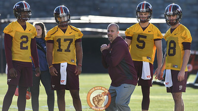 Virginia Tech offensive coordinator/ quarterbacks coach Brad Cornelsen demonstrates proper technique to his group of quarterbacks. (Michael Shroyer/ TheKeyPlay.com)