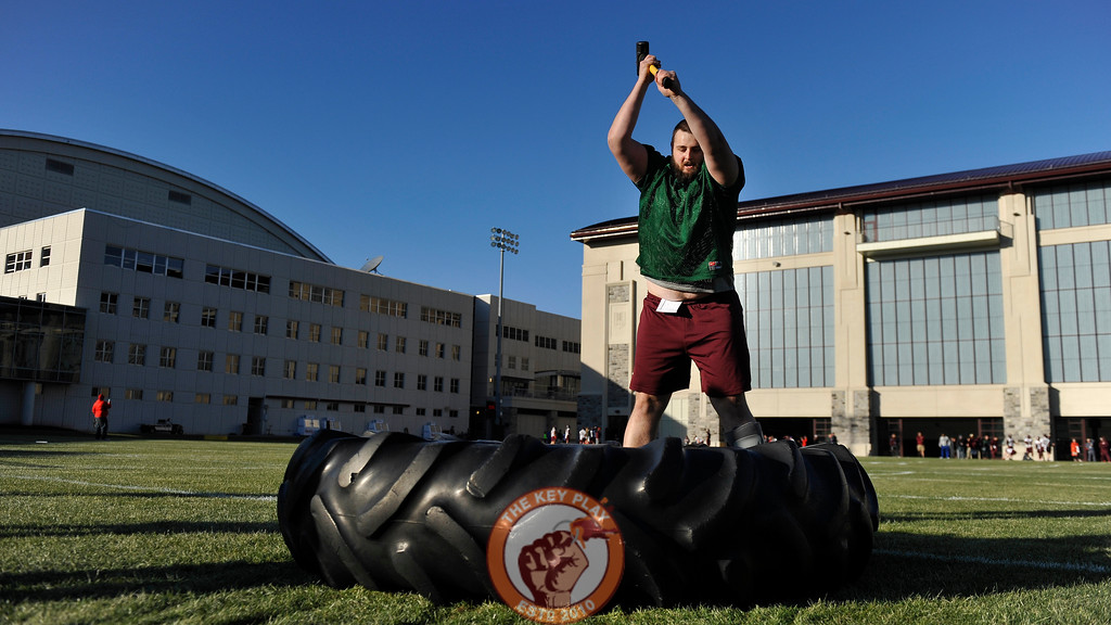 Virginia Tech Hokies tackle Parker Osterloh (67) repeatedly swings a sledge hammer at a giant tire during practice. (Michael Shroyer/ TheKeyPlay.com)