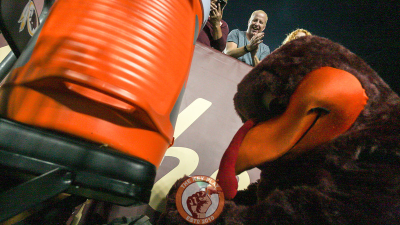 The Hokiebird gets some water from the team's supplies for a fan in the first row. (Mark Umansky/TheKeyPlay.com)