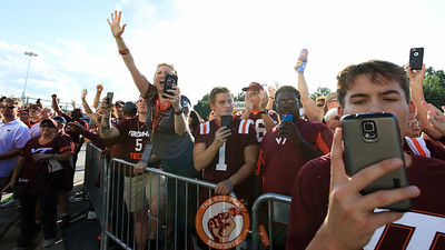 Hokies fans take photos and cheer as the team pulls into FedEx Field on their buses. (Mark Umansky/TheKeyPlay.com)