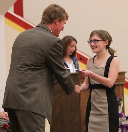 Roger Schneider | The Goshen News<br /> Kaylee Adelmann smiles as she receives the first eighth-grade graduation certificate Thursday from Principal Randy Miller.