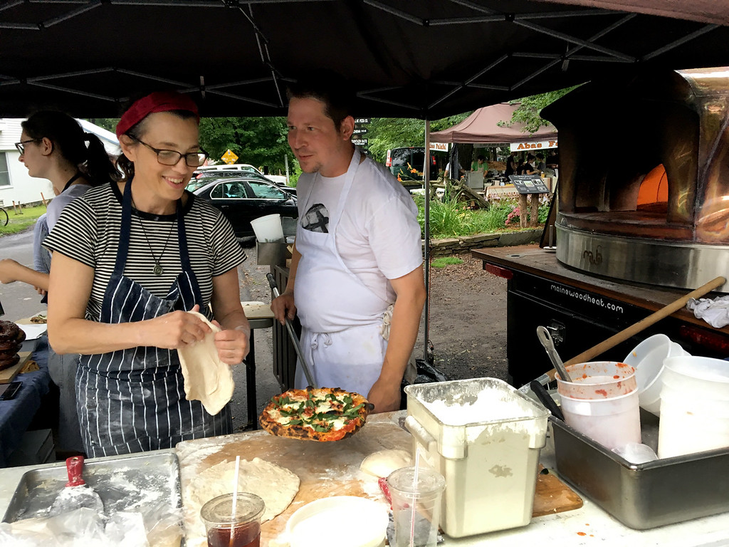""". Tania Barricklo-Daily Freeman                      Sharron Burns-Leader, left, co-owner of Bread Alone located in Woodstock, Boiceville and Lake Katrine, was at the weekly Woodstock Farm Festival Wednesday with Jesse Frederick , the chef at all three bakeries, where they made personal sized pizzas. Every week they make Margarita pizzas along with  a \""""market\"""" pizza, selecting vegetables from a vendor at the market that day. The pizzas are made in their mobile wood- fired pizza oven named Andre, seen at right ."""