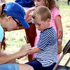 Justin Bawm, 3, from Yorkville, gets a Cubs logo painted on his arm at River Fest in downtown Yorkville on Saturday. His older sister Taylor, 5, standing behind him, got a rainbow painted on her arm.
