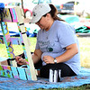Ashley Preciado, from the Fox River Academy of Music and Art, paints a pallet during River Fest on Saturday. The pallets, painted by members of the academy and the community, will be collected, turned into benches, and displayed in downtown Yorkville.