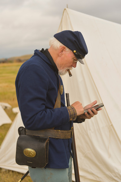 Justin Sheely | The Sheridan Press<br /> Reenactor Robert Kelleher of Billings, Montana, checks his cellphone prior to the reenactment battle during the 150-year anniversary of the Wagon Box Fight Saturday at the Fort Phil Kearny State Historic Site. The battle involved 32 United States soldiers and nearly 800 warriors on Aug. 2, 1867 approximately 30 miles south of Sheridan. The soldiers held off the attacks of the Native warriors with only six casualties.