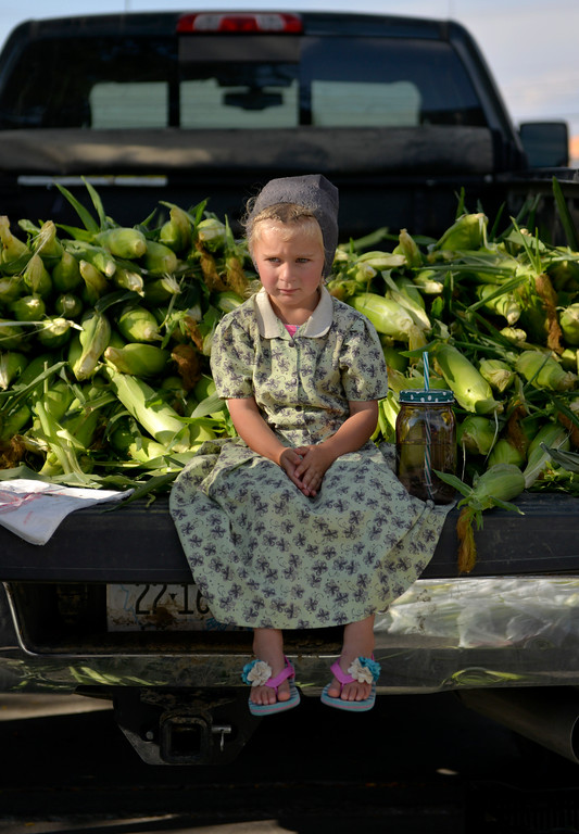 Justin Sheely | The Sheridan Press<br /> Three-year-old Hutterite Isabelle Walter of the 40 Mile Colony Ranch near Lodge Grass, Montana, waits on the tailgate during the weekly farmers market Thursday afternoon on Grinnell Plaza.