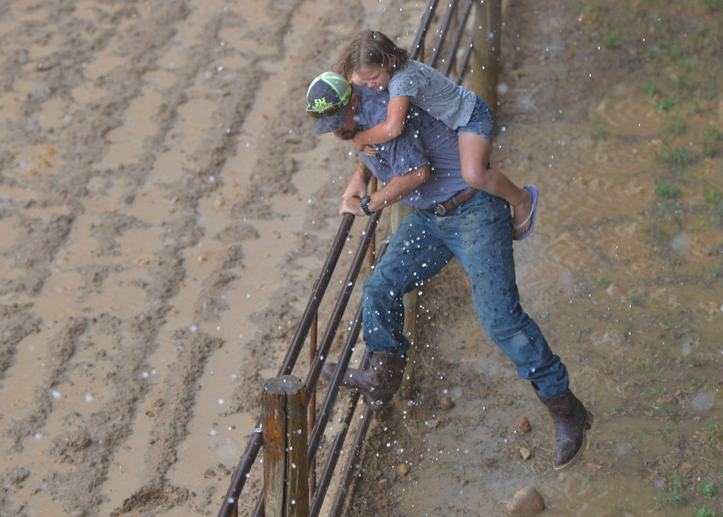 Justin Sheely | The Sheridan Press<br /> Brian Myers carries Jackie Myers to shelter as rain pours down during the Sheridan Cowgirls Association Rodeo Thursday at the Sheridan County Fairgrounds. The rodeo was cut short after the thunderstorm dumped rain and hail.