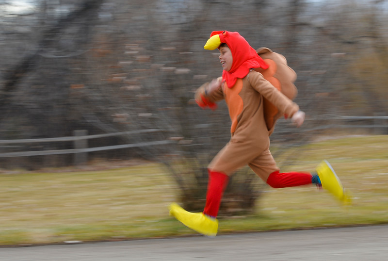 Justin Sheely | The Sheridan Press<br /> Eight-year-old Adam Baures runs ahead of the children's race for the annual Thanksgiving Day Turkey Trot Thursday at Kendrick Park. The event supports the track and cross-country programs at Sheridan High School and Sheridan Junior High School. Race participants also contributed to the high school's community food drive.