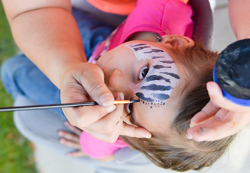 Justin Sheely | The Sheridan Press<br /> Four-year-old Paisley Fort looks up as she gets her face painted during Holy Name Catholic School's annual Fall Carnival and Chili Cook-off Saturday at Whitney Commons Park.