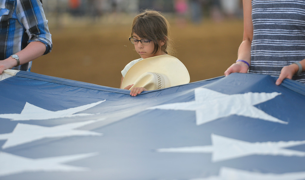 Justin Sheely | The Sheridan Press<br /> Nine-year-old Mary Garcia and others holds the national flag brought down by Dana Bowman as the announcer says a prayer during the Sheridan WYO Rodeo Friday at the Sheridan County Fairgrounds.