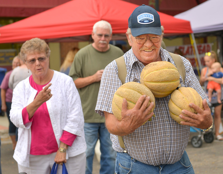 Justin Sheely | The Sheridan Press<br /> Mike Ligocki carries his purchase of cantaloupe as Coralee Davis, left, looks on during the last weekly Farmers Market of the season Thursday on Grinnell Plaza in downtown Sheridan.