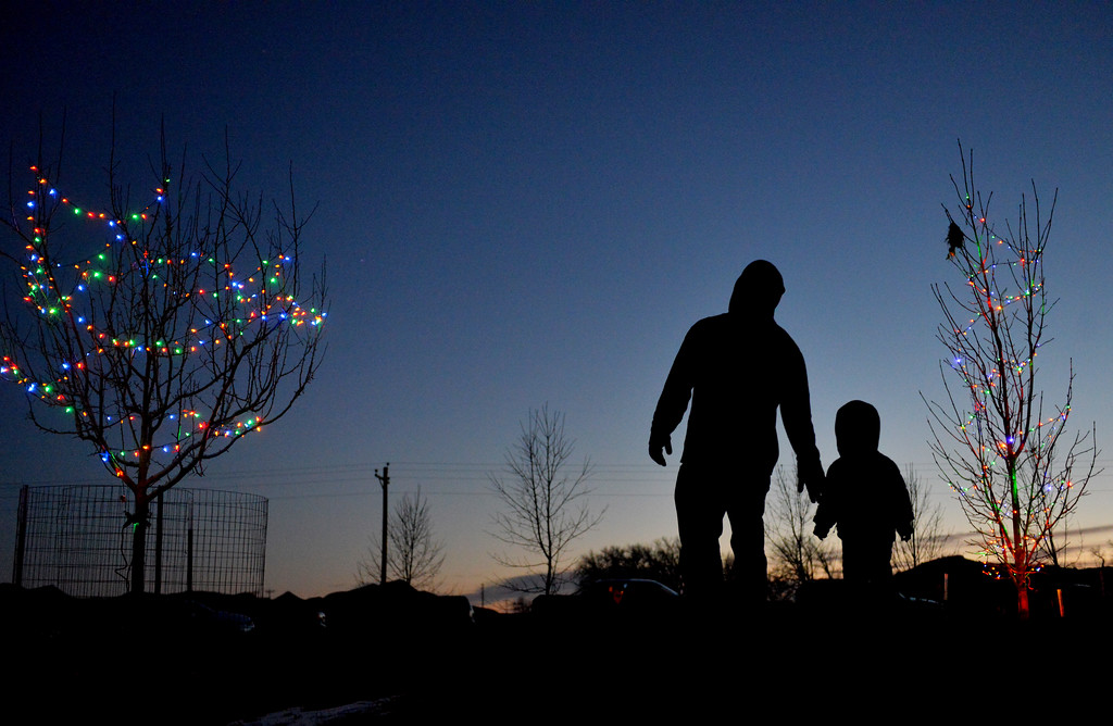 Justin Sheely | The Sheridan Press<br /> Guests walk through the lit trees during the 5th annual Ucross Christmas Celebration at the Raymond Plank Creative Center at Ucross Saturday, Dec. 9, 2017.