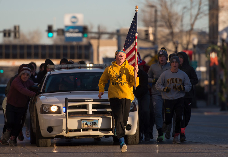 Justin Sheely | The Sheridan Press<br /> Hunter Goodwin carries the flag as the Broncs wrestling team push a Sheridan Police Department car Saturday morning on Main Street. The Sheridan High School wrestling team begin their season with the tradition of pushing a police car from the station to the Sheridan County Courthouse and back.