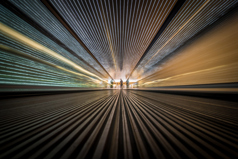 Perspective wide angle view of modern light blue illuminated and spacious high-speed moving commercial escalator