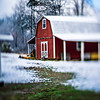 red little barn farm on winter landscape