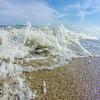 ocean waves crashing onto sandy beach shores