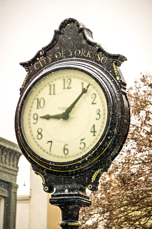 vintage historic street clock with snow falling in winter