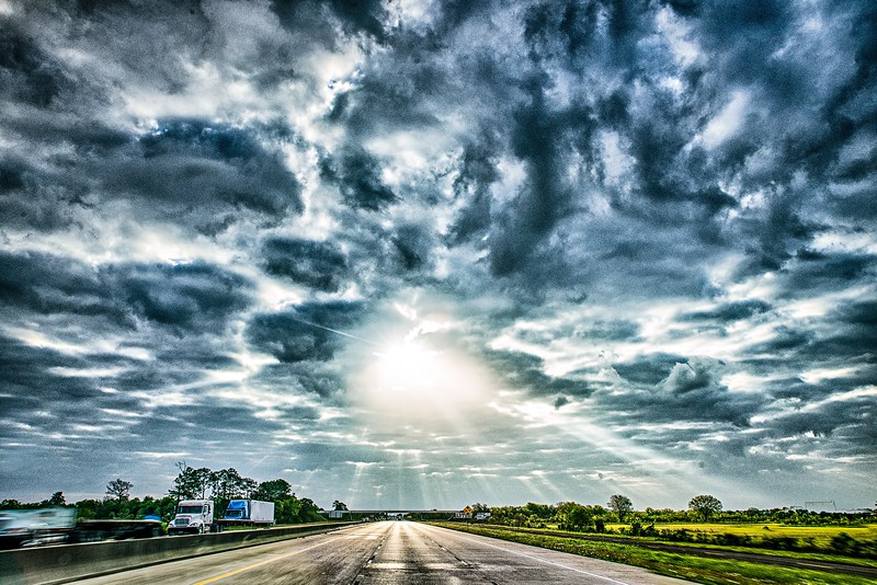 freeway through country landscape with dramatic skyes and sun rays