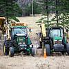 giant lawn mowers on farm field