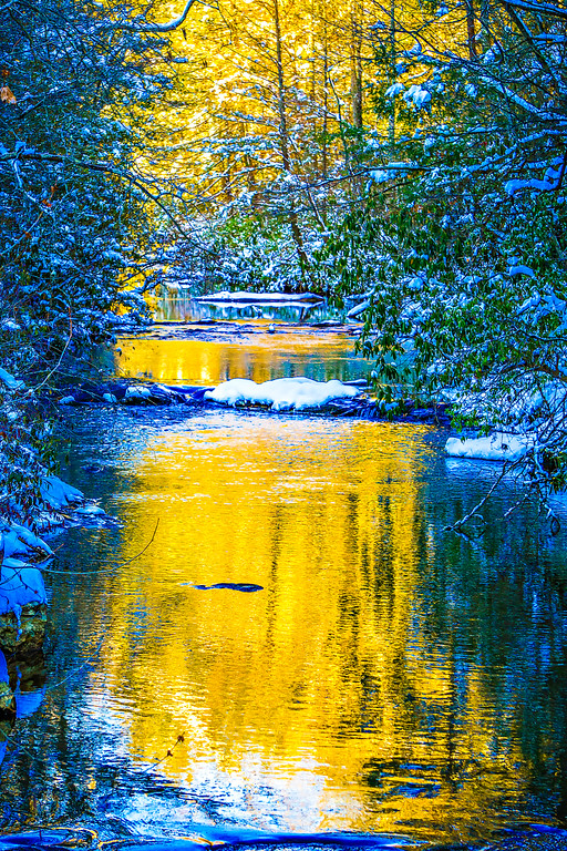 mountain stream at sunset with snow
