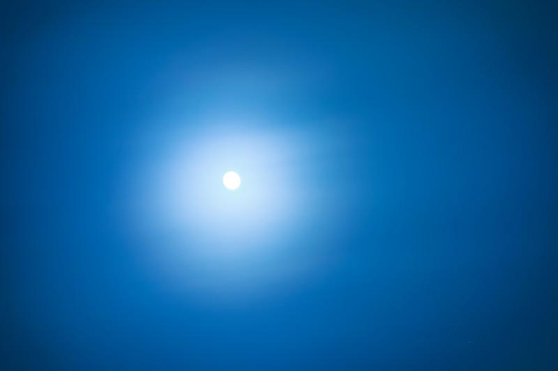 fuul moon behind cloudy hazy sky