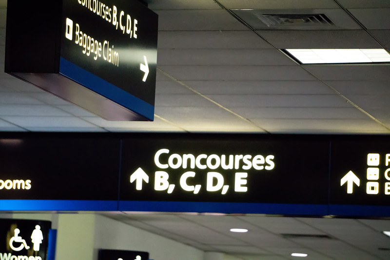 concourse sign and directional arrows at an airport