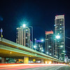 san francisco city skyline along side of highway traffic at night