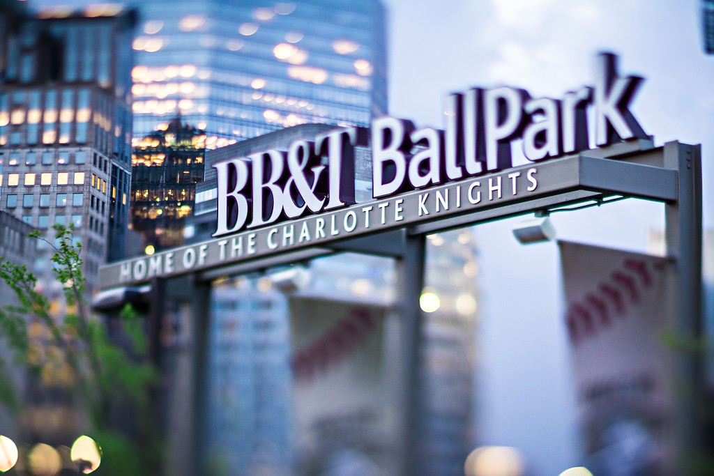 April 2017 Charlotte NC USA - BB&T baseball park sign and charlotte skyline with tilt effect in the morning