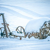old abandoned till cultivator covered in snow on farm
