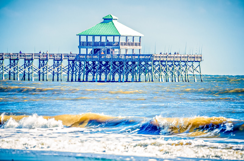 folly beach fishing pier and waves crashing into land on sunny day