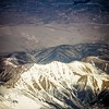 flying over rocky mountains in spring at day time