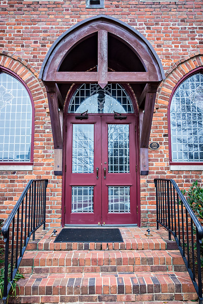 wooden door and entrance to an old brick church