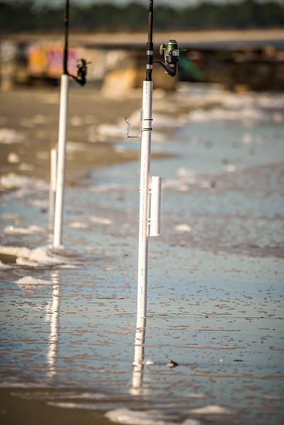 fishing rods dug into ocean beach coast