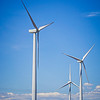 wind turbines generating electricity on a windy sunny day
