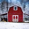 red little barn farm on winter landscape