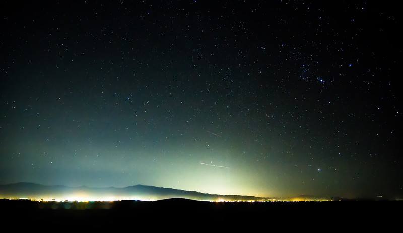 night sky in death valley with pahrump city lights in distance