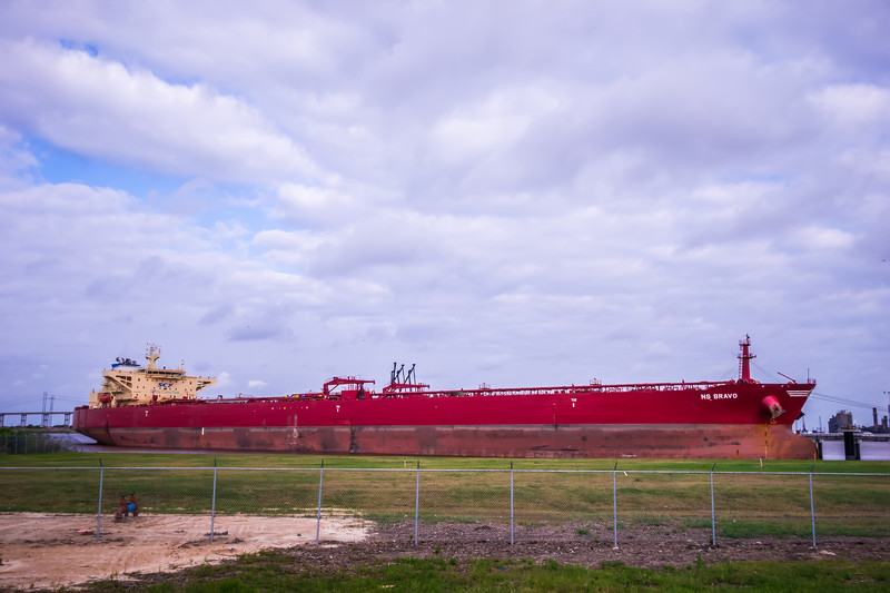 large red cargo ship parked on gulf of mexico coast