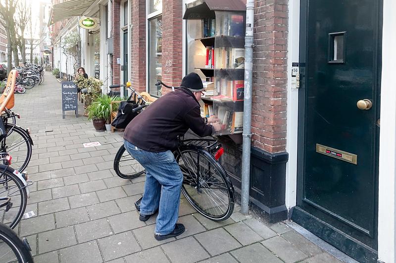 Nederland, Amsterdam, man zoekt een boek in een openbare boekenkast,4 januari 2017, foto: Katrien Mulder