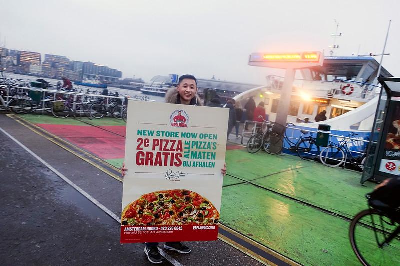 Nederland, Amsterdam, man loopt rond met een reclamebord van een pizzeria in Amsterdam Noord, 30 januari 2017, foto: Katrien Mulder