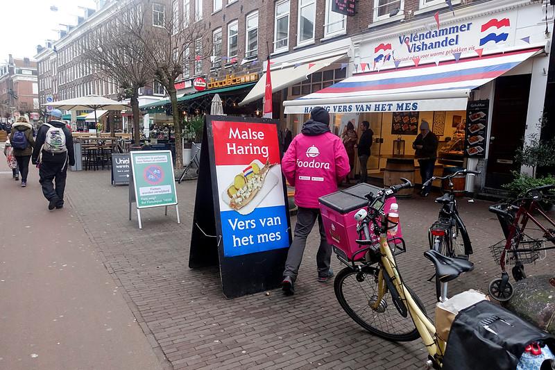 Nederland, Amsterdam, koerier van het eigentijdse  maaltijd-aan-huis-bezorg-bedrijf Foodora gaat een ouderwets broodje haring halen bij de visboer in de pijp, 31 januari 2017, foto: Katrien Mulder