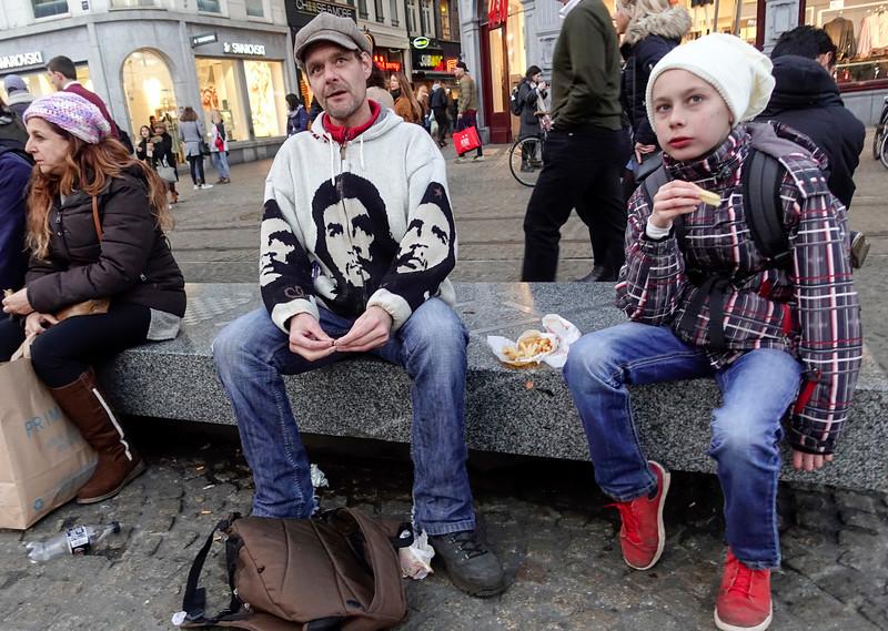 Nederland, Amsterdam, Vader Jean Paul en   zoon Thibaut uit Limburg doen hun jaarlijkse dagje Amsterdam, rondkijken op de Dam, slenteren op de wallen, patatje eten, het is weer es wat anders dan de provincie.  De Che Guevara hoodie heeft Jean Paul ergens in Azie op de kop getikt, is met de hand gebreid, hij kocht hem gewoon omdat het een leuk vest was, pas later is hij het een en ander aan de weet gekomen over Che Guevara., 18 februari 2017, foto: Katrien Mulder