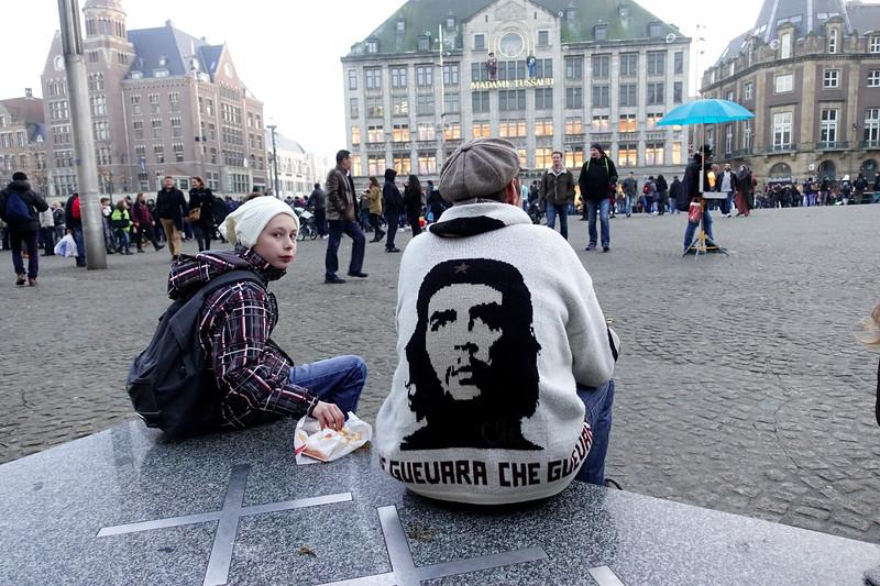 Nederland, Amsterdam, Vader Jean Paul en   zoon Thibaut uit Limburg doen hun jaarlijkse dagje Amsterdam, rondkijken op de Dam, slenteren op de wallen, patatje eten, het is weer es wat anders dan de provincie.  De Che Guevara hoodie heeft Jean Paul ergens in Azie op de kop getikt, is met de hand gebreid, hij kocht hem gewoon omdat het een leuk vest was, pas later is hij het een en ander aan de weet gekomen over Che Guevara. 18 februari 2017, foto: Katrien Mulder