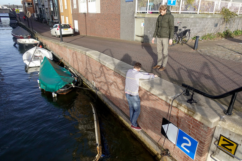 Nederland, Amsterdam, Java eiland, 21 februari 2017, Erik en Eyves proberen uit de goedheid van hun hart, geheel belangloos, en met gevaar voor eigen leven, gewoon voor de lol dus, een gezonken sloepje, van wie ze de eigenaar niet eens kennen,  boven water te krijgen, Erik and Eyves try out of the goodness of their hearts, entirely disinterested, and risking their lives, so just for fun  ,  to get above the water a sunken sloop, whose owner they do not even know  ,foto: Katrien Mulder
