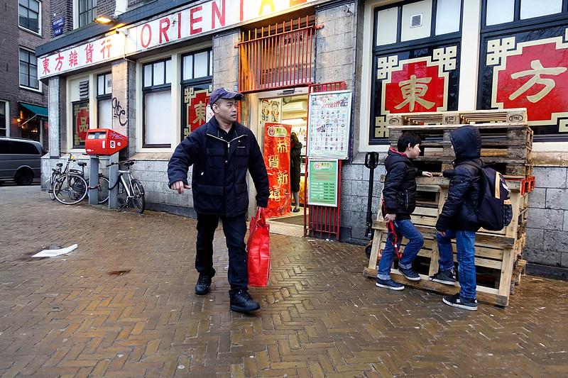 Nederland, Amsterdam, Chinese man verlaat de Chinese supermarkt op de Nieuwmarkt, 27 februari 2017, foto: Katrien Mulder